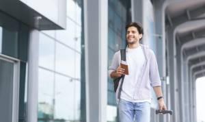 Cheerful guy going to flight registration, enjoying future travel