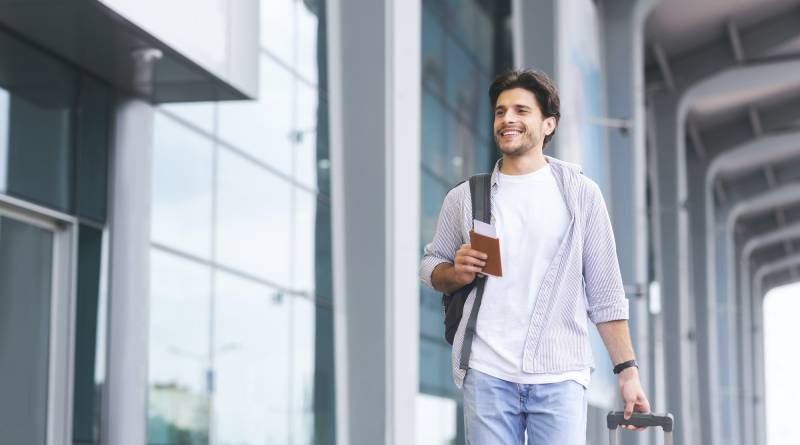 Cheerful guy going to flight registration, enjoying future travel
